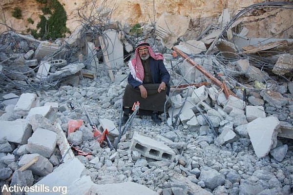 A member of the Jahalin Bedouin sits on the remains of his demolished home in Al Eizariya, West Bank, March 18, 2009. (photo: Anne Paq)