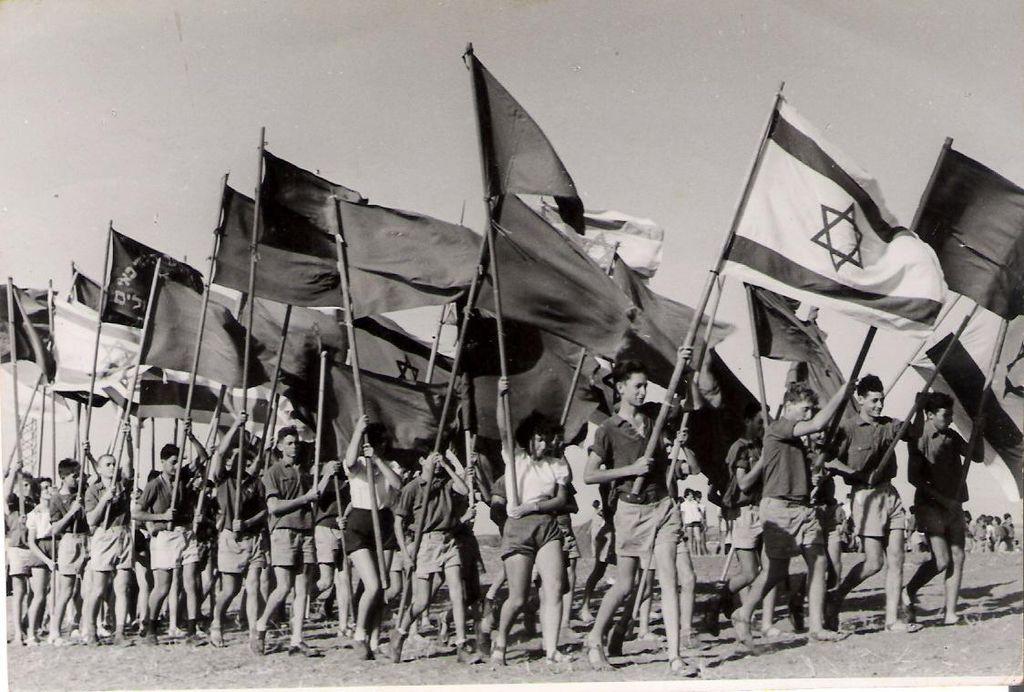 Kibbutz members march in a 1951 ceremony. (אביבה שני בית חרות/CC BY 2.5)