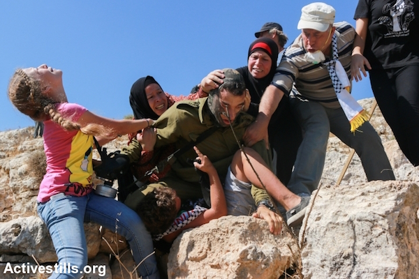 Members of the Tamimi family prevent an Israeli solider from arresting Mohammed Tamimi, 12, during the weekly protest against the occupation in the West Bank village of Nabi Saleh, August 28, 2015. (Muhannad Saleem/Activestills.org)