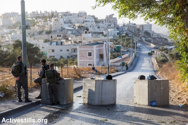 Israeli police stand at a roadblock meant to stop vehicular traffic going in and out of the Jabel Mukaber neighborhood of East Jerusalem, October 15, 2015. Following a spate of over a dozen stabbing attacks carried out by Palestinian residents of East Jerusalem, Israel blocked off and erected checkpoints at the entrances and exits of most Palestinian neighborhoods of Jerusalem. Many of the checkpoints are meant to stop cars from entering or exiting the neighborhoods. (Yotam Ronen/Activestills.org)