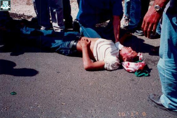 An Arab youth lies bloodied on the ground after being shot by Israeli Border Police. (photo courtesy of Adalah)
