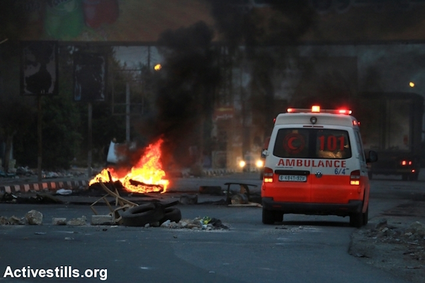A Palestinian ambulance evacuates wounded protesters during clashes between Palestinian youths and Israeli army forces at the Huwwara checkpoint near Nablus, West Bank, October 12, 2015. (Ahmad al-Bazz/Activestills.org)