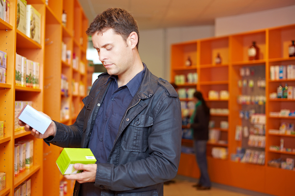 Illustrative photo of a man reading the labels of two products. (Shutterstock.com)