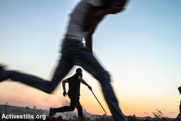 Palestinians run from tear gas and gunfire during a protest near the Gaza border, east of Al Bureij refugee camp, October 16, 2015. The Israeli army killed at least two people during the protest. (Ezz Zanoun/Activestills.org)