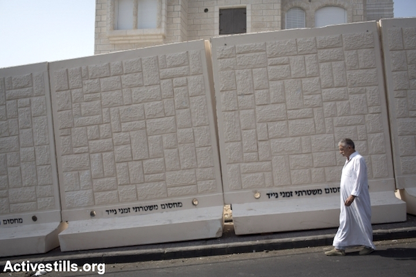 A Palestinian man walks past a newly erected temporary concrete wall that  in the East Jerusalem neighborhood of Jabel Mukaber October 19, 2015. (Oren Ziv/Activestills.org)