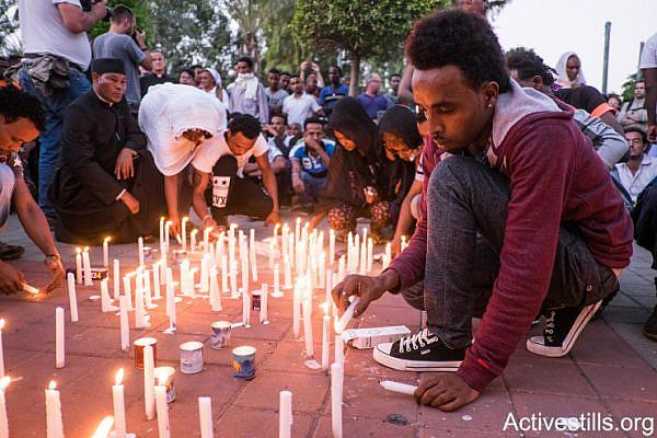 Members of the Eritrean community in Israel light candles at a memorial service for a memorial ceremony for asylum seeker Habtom Zarhum in Levinsky park in south Tel Aviv, October 21, 2015. (Oren Ziv/Activestills.org)