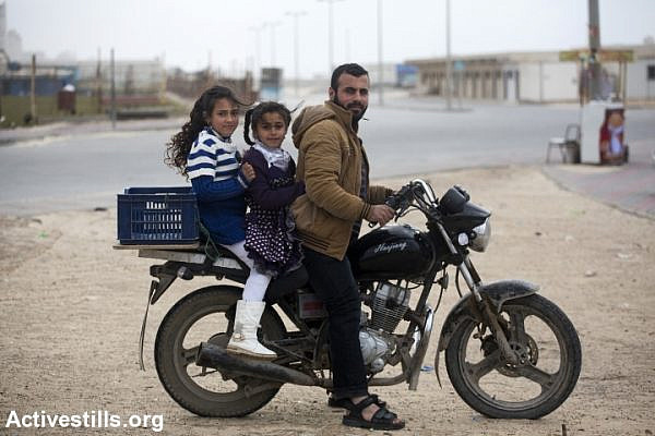 A Palestinian carries his two daughers on his motorcycle in the harbour of Gaza city, February 13, 2015. The sea remains one of the few open space where Palestinians can go and try to relax despite a very dire humanitarian situation and the trauma following the last summer Israeli military offensive. (photo: Anne Paq/Activestills.org)