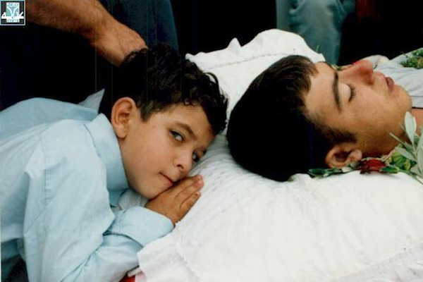A child lays his head next to one of the Palestinians killed by Israeli police in early October 2000. (Photo courtesy of Adalah.)