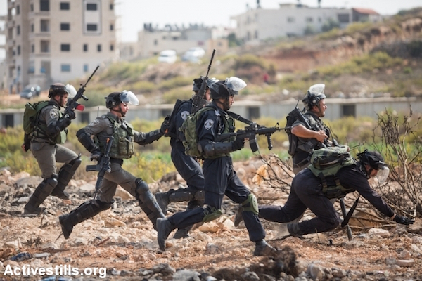 Israeli police and Border Police officers run toward Palestinian youths during clashes, October 12, 2015. (Yotam Ronen/Activestills.org)