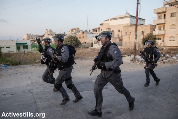 Israeli riot police run during clashes in the Shuafat neighborhood of East Jerusalem, October 5, 2015. (Faiz Abu Rmeleh/Activestills.org)
