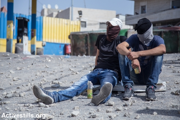 Palestinian youths hold Molotov cocktails on as they sit not he sidelines of clashes taking place in the East Jerusalem neighborhood of Issawiya, October 4, 2015. (Faiz Abu Rmeleh/Activestills.org)