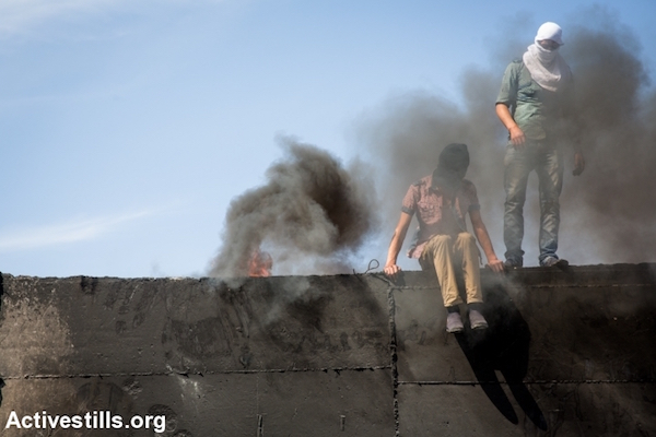 Palestinian protesters sit on top of the separation wall during clashes with Israel security forces in Abu Dis, east of Jerusalem, October 11, 2015. (Yotam Ronen/Activestills.org)