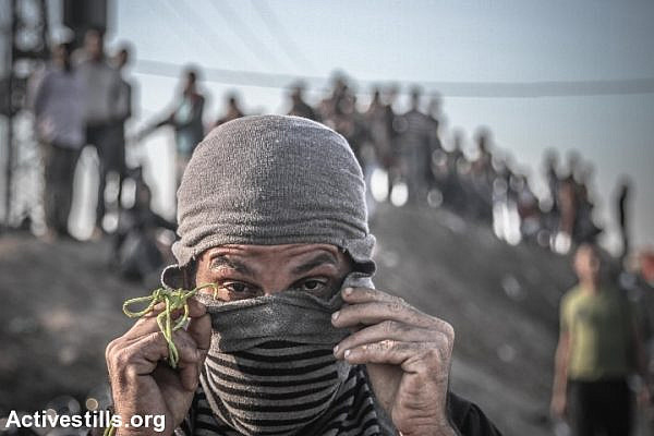 A Palestinian adjusts his mask during a protest near the Gaza border Strip, near Nahal Oz crossing, October 30, 2015. Since the beginning of October, more than 60 Palestinians have been killed in shootings and clashes with Israeli forces in the occupied Palestinian territories and Israel, while eight Israelis have been killed in knife and gun attacks. (photo: Ezz Zanoun/Activesills.org)
