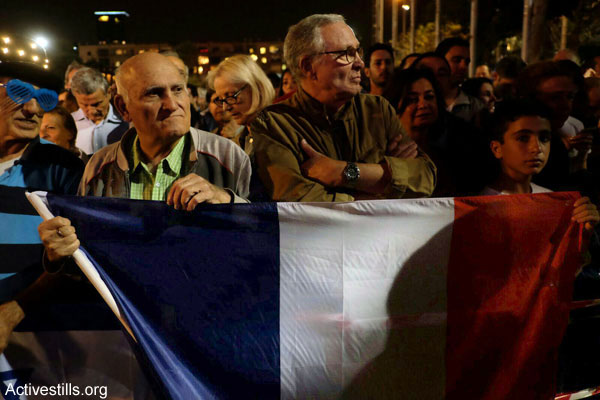 Israeli men stand with a French flag at the Tel Aviv memorial for victims of the Paris terror attacks, November 14, 2015. (Yotam Ronen/Activestills.org)