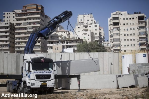 Building the separation barrier around Shuafat refugee camp, East Jerusalem, 2013. (photo: Oren Ziv/Activestills.org)