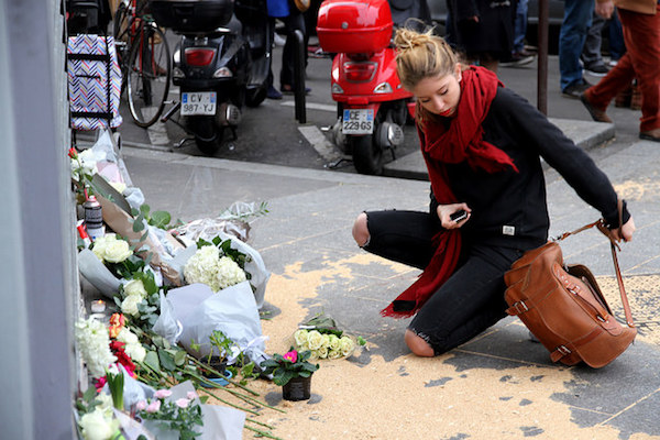 A woman lays flowers at an impromptu memorial a day after the Paris terror attacks, Le Petit Cambodge / Carillon, November 14, 2015. (Maya-Anaïs Yataghène/CC)