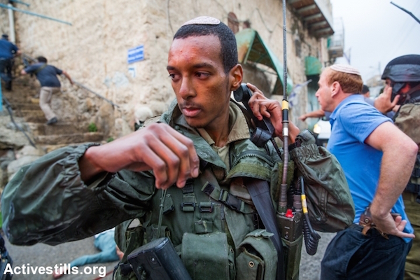 Israeli soldiers gather around the body of a Palestinian man who allegedly tried to stab a soldier at the Jewish settlement in the center of the Israeli-occupied city of Hebron, West Bank, on October 29, 2015. The city of Hebron has seen escalating violence in last weeks. (Yotam Ronen/Activestills)