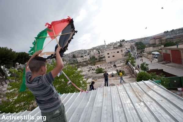 A boy launches a Palestinian flag kite during an event commemorating Nakba Day, Aida Refugee Camp, Bethlehem, West Bank, May 14, 2012. (Ryan Rodrick Beiler/Activestills.org)