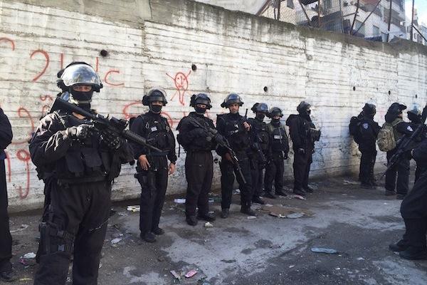 Israeli security forces line up in a street in Shuafat refugee camp during a home demolition, East Jerusalem, December 2, 2015.