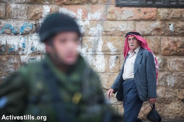 A elderly Palestinian man walks past an Israeli soldier stationed in the center of the occupied city of Hebron, West Bank, October 29, 2015. (Yotam Ronen/Activestills.org)