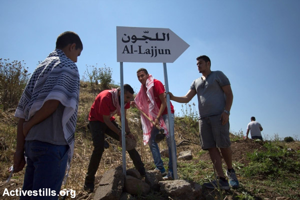 Palestinians put a sign marking the destroyed village of Lajjun in northern Israel, Nakba Day, May 15, 2015. (Photo by Omar Sameer/Activestills.org)