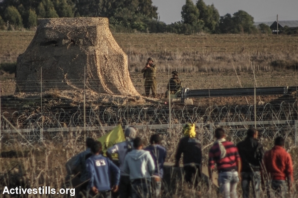 An Israeli soldier raises his rifle toward unarmed Palestinian protesters along the border fence separating Israel and Gaza, Gaza Strip, near the Nahal Oz crossing, October 30, 2015. (Ezz Zanoun/Activestills.org)