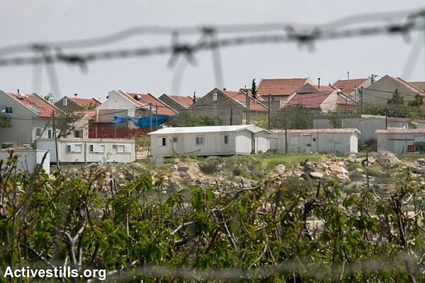 Mobile homes and fruit trees represent the expanding edges of the Israeli settlement of Ma'on, which is taking land from the South Hebron Hills village of Al Tuwani, West Bank, April 2, 2014. (Ryan Rodrick Beiler/Activestills.org)