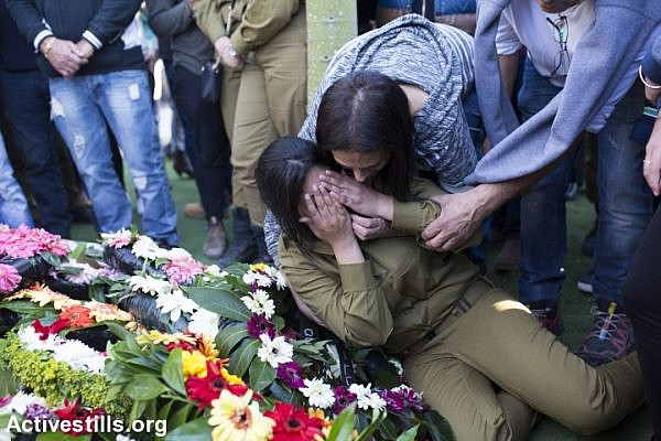 An Israeli soldier mourns beside flowers placed on the grave of Israeli border policewoman, Hadar Cohen, 19, during her funeral at the military cemetery in Yehud, near Tel Aviv, Israel, February 4, 2016. (photo: Oren Ziv/Activestills.org)