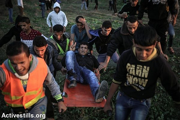 Palestinians carry an injured protester during clashes with Israeli forces near the Israel-Gaza border, near Nahal Oz crossing, Nobember 20, 2015. (Ezz Zanoun/Activestills.org)