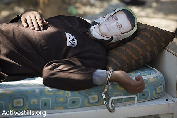 A Palestinian man wearing the likeness of hunger striking Palestinian journalist Muhammad al-Qiq lies shackled to a bed. Al-Qiq has been on hunger strike for 83 days in protest of his administrative detention. Bil'in, February 19, 2016. (Oren Ziv/Activestills.org)