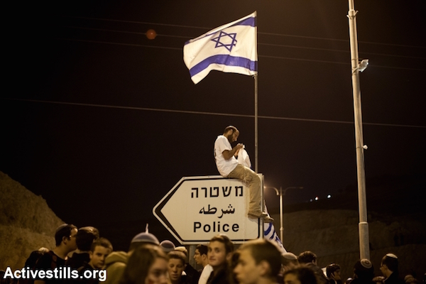 Right-wing Israeli settlers demonstrate after marching from Ma'aleh Adumim settlement to the E1 area on the eastern outskirts of Jerusalem, during a protest calling for an expansion of Jewish settlements in E1, West Bank, February 13, 2014. (Activestills)
