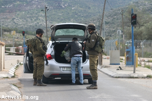 Israeli soldiers inspect a vehicle at the Enav checkpoint separating the West Bank Palestinian cities of Nablus and Tulkarem, January 11, 2016. (Ahmad Al-Bazz/Activestills.org)