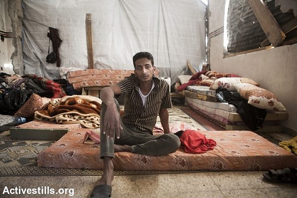 Fadi al Najjar, 24, in his destroyed home in the village of Khuza'a, eastern Gaza Strip, November 7, 2014. Six family members stay in the living room, which is the only room which was not destroyed. Fadi lost all his money and his animals, during the last Israeli assault. He is now contemplating on getting married and lives in the caravan which has been allocated to his father Adnan. Big holes in the walls have been barely covered by pieces of wood and plastic sheet. Many Palestinians in the Gaza Strip face hard living conditions following the seven-week Israeli offensive during which 2,131 Palestinians were killed, and an estimate of 18,000 housing units have been either destroyed or severely damaged, leaving more than 108,000 people homeless. (photo: Anne Paq/Activestills.org)