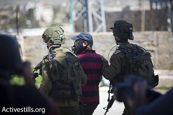 Israeli soldiers arrest a Palestinian photographer during a demonstration in the West Bank city of Hebron, February 26, 2016. (photo: Oren Ziv/Activestills.org)