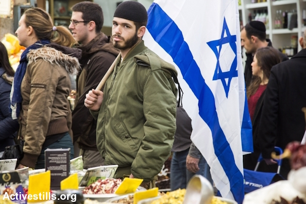 "A soldier shows his support as Michael Ben Ari, leader of Otzma Yehudit nationalist party is accompanied by Benzi Gopstein, head of the anti-miscegenation group Lehava, to walk in Jerusalem's Mahane Yeיuda market during an election campaign, January 16, 2015. Otzma Yehudit, meaning ""Jewish strength,"" which failed to make the Knesset at the last elections, advocates for transferring Palestinians out of Israel and the West Bank."