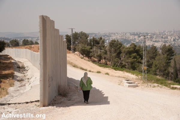 A Palestinian woman walks along an unfinished section of the separation barrier in the West Bank town of al-Walaja. (Ryan Rodrick Beiler/Activestills.org)