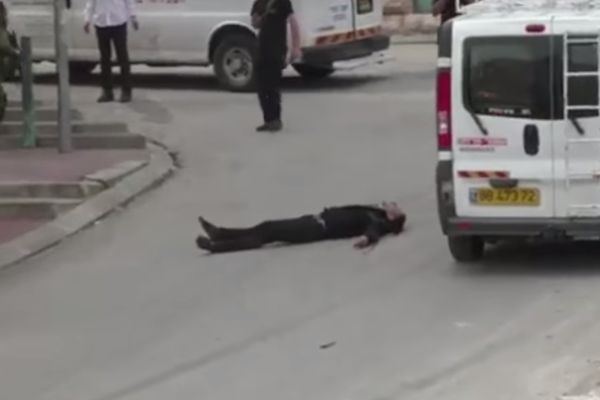 A Palestinian man seen laying on the ground seconds after being shot in the by an IDF soldier. (YouTube screenshot)