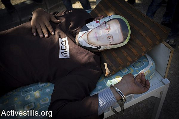 A Palestinian man lying on a bed wears a face covering depicting hunger striking Palestinian journalist Mohammed al-Qiq, on February 19, 2016, during a demonstration protest marking 11 year for the struggle against the wall in the West Bank village of Bilin, near Ramallah. Israel's Supreme Court said on February 16, 2016, the Palestinian hunger striker who has fasted over 80 days must stay in the northern Israeli hospital where he is being held, after a compromise bid failed. (Activestills.org)