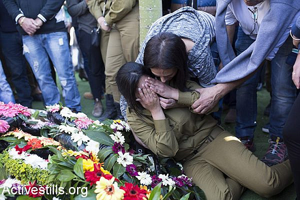 Israeli soldier mourn beside flowers placed on the grave of Israeli border policewoman, Hadar Cohen, 19, during her funeral at the military cemetery in Yehud, near Tel Aviv, Israel, February 4, 2016. Three Palestinians killed the Israeli border policewoman and wounded another before being shot dead by nearby officers at Damascus gate IN Jerusalem's Old City on February 3, 2016. (Activestills.org)