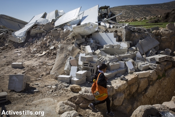 A Palestinian girl walks back from school to her demolished home after it was torn down by Israeli bulldozers in the village of Khirbet al-Halawah in firing zone 918, which includes several villages, south of Hebron, West Bank, February 3, 2016. Israeli forces demolished at least a 23 buildings in the military zone in the southern West Bank, leaving several families homeless. Israel has carried out a long campaign to relocate the residents of the area, which was declared a military zone by the Israeli government in the 1970s.
