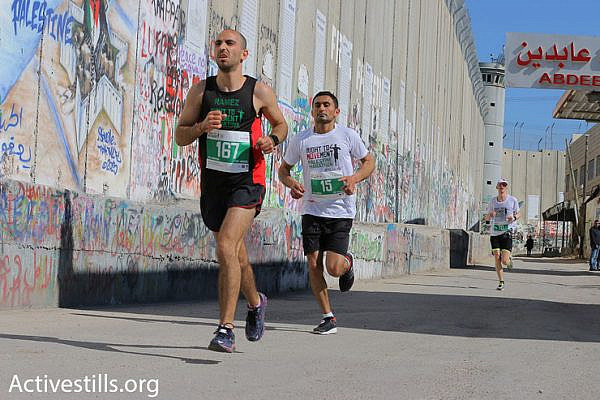Participants in the 2016 Palestine Marathon run along Israel's concrete separation wall, Bethlehem, West Bank, April 1, 2016. (Ahmad al-Bazz/Activestills.org)