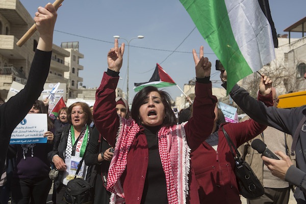 Palestinian women protest against the occupation on International Women's Day at the Qalandiya military checkpoint separating Jerusalem and Ramallah, March 7, 2015. (Anne Paq/Activestills.org)