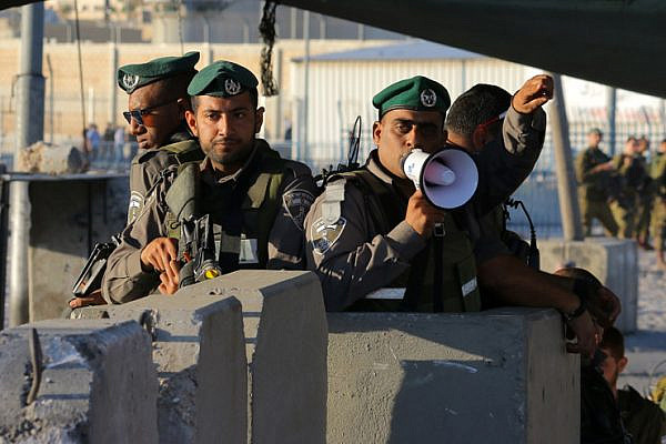 Israeli Border Police direct Palestinian worshipers through the Qalandiya checkpoint separating Ramallah and Jerusalem on their way to pray at Al-Aqsa Mosque for the second Friday of Ramadan, June 17, 2016. (Ahmad Al-Bazz/Activestills.org)