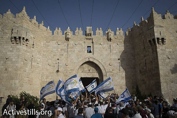 Nationalist Jewish Israelis, largely bussed-in yeshiva students, enter the Muslim Quarter of Jerusalem's Old City through Damascus Gate on Jerusalem Day, June 5, 2016. (Oren Ziv/Activestills.org)