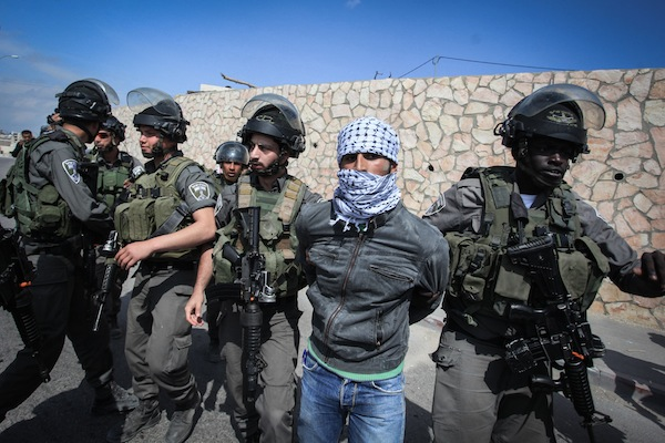 Israeli border policemen detain a Palestinian protester during a protest against what Palestinians say is land confiscation by Israel for Jewish settlements, near the West Bank town of Abu Dis near Jerusalem March 17, 2015. (photo by STR/Flash90)