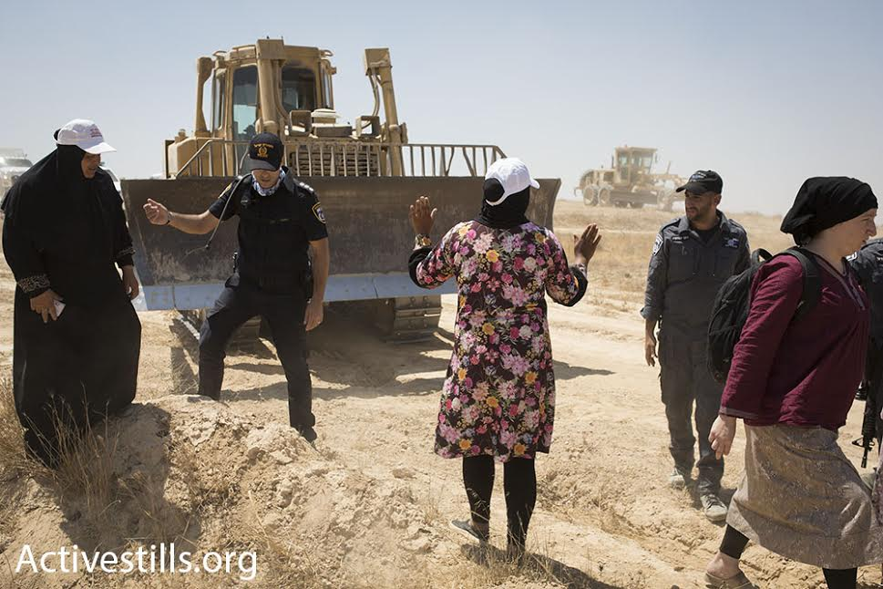 A Bedouin woman attempts to block a bulldozer during a march in the unrecognized village of Al-Araqib, Negev Desert, July 24, 2016. (photo: Oren Ziv/Activestills.org)