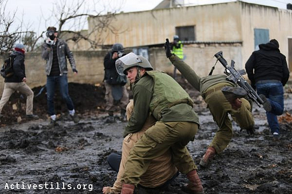 Israeli soldiers arrest a Palestinian youth during the weekly protest against the occupation, in the West Bank village of  Kafr Qaddum, January 16, 2015.