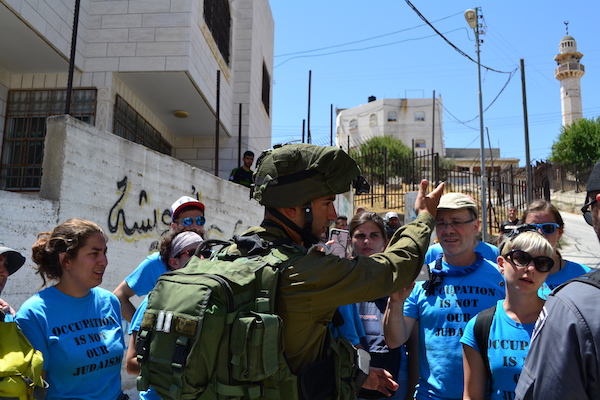 An Israeli soldier attempts to stop activists with the Center for Jewish Non-Violence in the West Bank city of Hebron, July 15, 2016. (Dahlia Scheindlin)