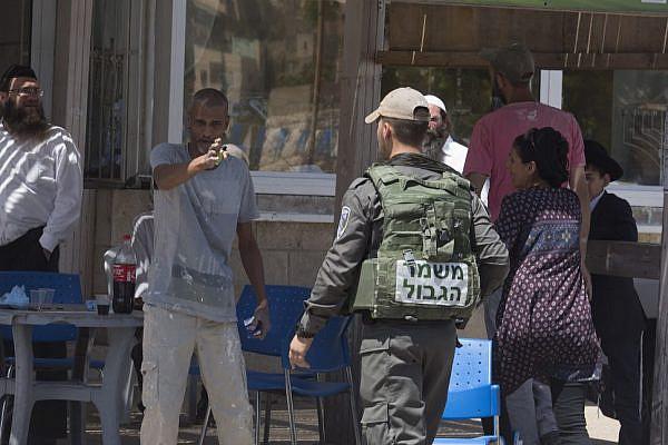Settlers attack Activestills photographer Oren Ziv and Breaking the Silence activist Yehuda Shaul during a tour of Hebron with famed Irish novelist Colm Tóibín, July 12, 2016. (photo: Oren Ziv/Activestills.org)