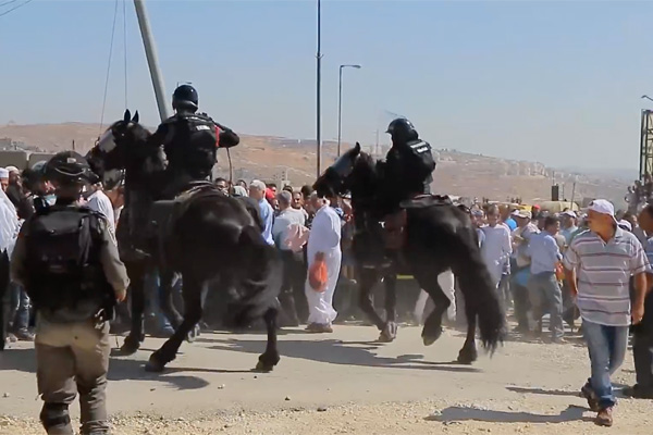 Mounted Israeli Border Police charge a crowd of Palestinians hoping to cross into Jerusalem to pray at al-Aqsa Mosque, July 1, 2016. (Screenshot/Activestills.org)
